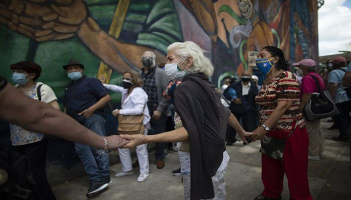 (Caracas, Venezuela) Elderly people hold hands to avoid others from cutting into the queue as they wait outside the Alba Caracas hotel to be vaccinated during a massive campaign for seniors in Caracas. || Photograph: Ariana Cubillos/AP