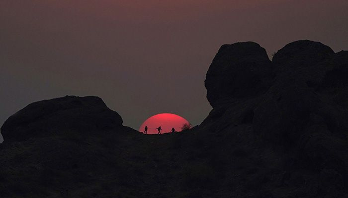 Hikers pause to watch the sunset at Papago Park during a heat wave where temperatures reached 115 degrees in Phoenix, Arizona, on June 15, 2021. || Photo: AP
