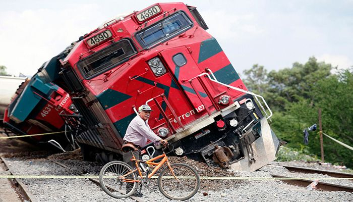 A man with a bicycle passes by a train that had derailed in the community of San Isidro Mazatepec in Tala, State of Jalisco, Mexico, on June 15, 2021. The freight train derailed and toppled onto houses alongside the tracks on Tuesday, killing one resident and injuring three others, emergency services said. || Photo: AP