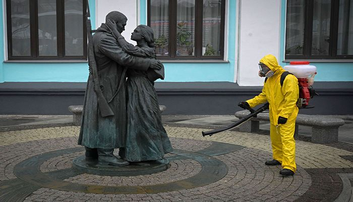 A serviceman of the Russian Ministry for Civil Defense, Emergencies, and Elimination of Consequences of Natural Disasters, wearing protective gear, disinfects Moscow's Belorussky railway station next to a statue on June 11, 2021. || Photo: AP