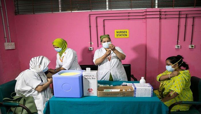 (Dhaka, Bangladesh) Medical workers distribute doses of the Pfizer vaccine. (Photograph: Allison Joyce)