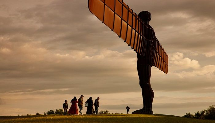 (Gateshead, England) Visitors walk by the Angel of the North statue looking out over the northeast region, which is currently the area in England worst affected by coronavirus. (Photograph: The Guardian)