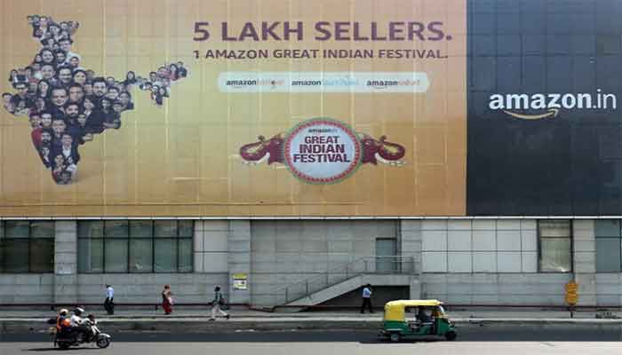 People move past a hoarding of Amazon India outside a metro rail station in New Delhi, India, October 23, 2019. || Photo:  Reuters