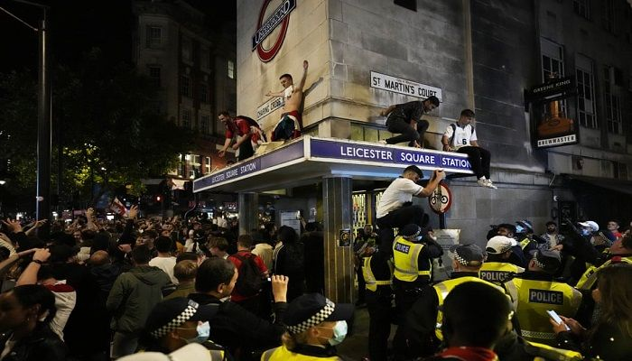 (London, England) Fans celebrate on the roof of Leicester Square underground station after England won the Euro 2020 semi-final against Denmark. (Photograph: Matt Dunham)