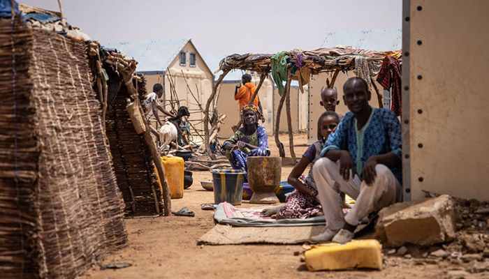 (Goudebo, Burkina Faso) Refugees sit by their shelter in Goudebo, a camp that is home to more than 11,000 Malian refugees in northern Burkina Faso, on International Refugee Day.    Photograph: AFP