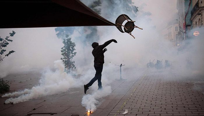 (Nantes, France)A demonstrator throws a chair towards anti-riot gendarmes during a protest to mark the second anniversary of the death of Steve Maia Canico, who died after falling in the river following a police raid during the Fete de la Musique.    Photograph: AFP