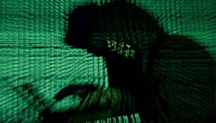 A man holds a laptop computer as cyber code is projected on him in this illustration picture taken on May 13, 2017. || Photo: Reuters