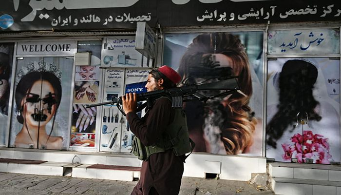 (Kabul, Afghanistan) A Taliban fighter walks past a beauty salon on which the images of women have been defaced (Photograph: Wakil Kohsar/AFP/Getty Images)