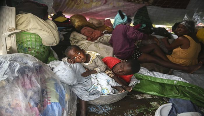 (Les Cayes, Haiti) People displaced by the earthquake huddle in a shelter made of blankets after Tropical Storm Grace lashed the south of the country (Photograph: Joseph Odelyn/AP)