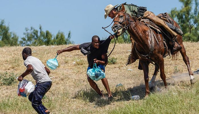 (Texas, US) A mounted United States Border Patrol agent attempts to stop a Haitian migrant from entering an encampment on the banks of the Rio Grande near the Acuna Del Rio International Bridge.    Photograph: Paul Ratje/AFP/Getty Images