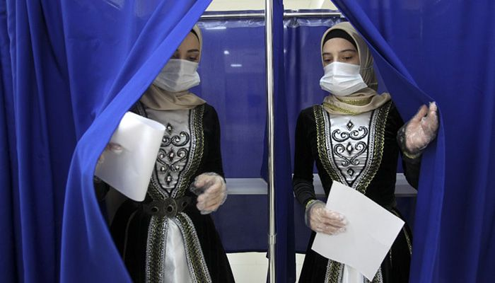 (Grozny, Russia) Chechen women in national costume leave a polling booth during the Parliamentary elections. Russia has begun the third day of voting for a new parliament.    Photograph: Musa Sadulayev/AP