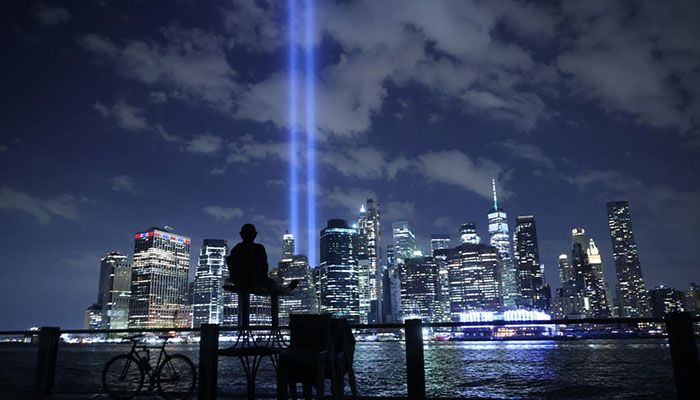 (New York City, US) A person watches the Tribute In Light shine into the sky from Lower Manhattan during a test before the 20th anniversary of the September 11 terrorist attacks || Photograph: Chip Somodevilla/Getty Images