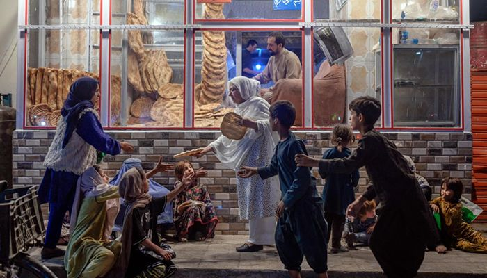 (Kabul, Afghanistan) A woman gives bread to young people in need in front of a bakery || Photograph: Bülent Kılıç/AFP/Getty