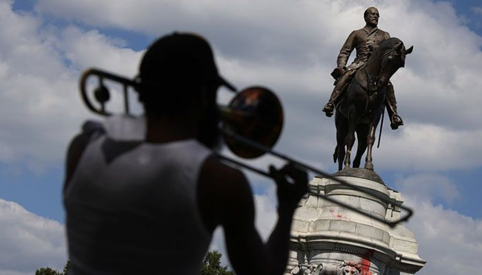 (Richmond, Virginia, US) A musician plays trombone near the statue of Robert E Lee on Monument Avenue in Richmond before its removal || Photograph: Alex Wong/Getty Images