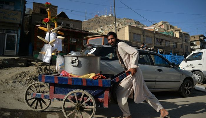 A vendor selling corns pushes his handcart along a street in Kabul on September 13, 2021. || AFP Photo: Collected