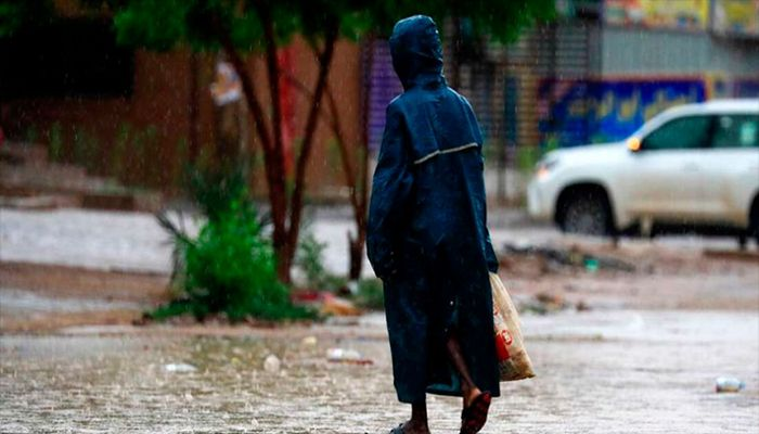 A woman walks along a flooded street in Khartoum after torrential rain fell on the Sudanese, August 8, 2021.    AFP Photo: Collected