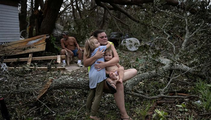 (Golden Meadow, Louisiana, US) Tiffany Miller is embraced by her daughter Desilynn as she holds her one-year-old godchild Charleigh, after the family returned to their destroyed home in the aftermath of Hurricane Ida    Photograph: Adrees Latif/Reuters